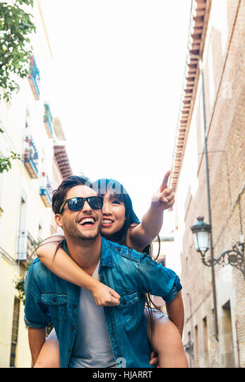 Happy loving couple. Happy young man piggybacking his girlfriend while pointing out at front - Stock Image