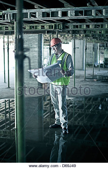 Construction worker reading blueprints - Stock-Bilder