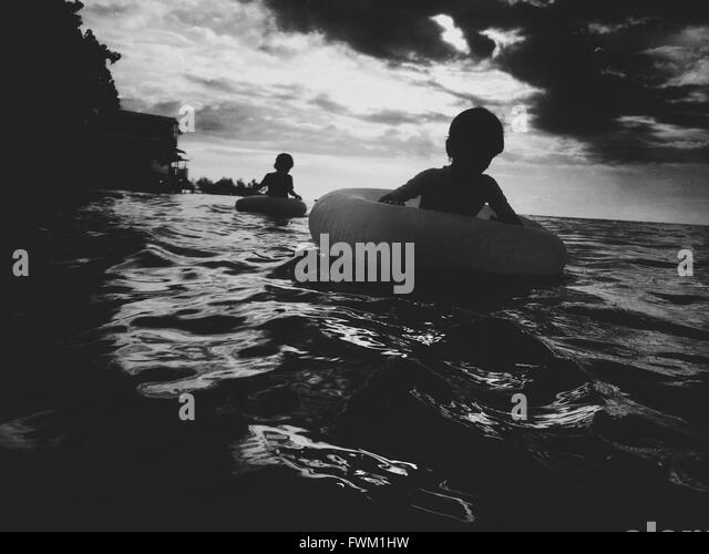 Silhouette Children Swimming With Inflatable Rings In Sea - Stock Image
