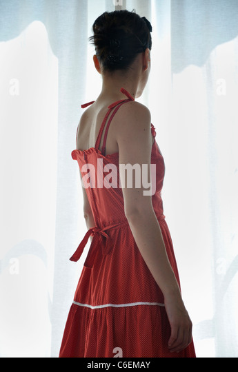 Young woman standing at the window - Stock Image