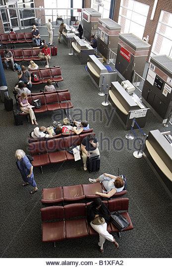 Arkansas Bentonville Northwest Arkansas Regional Airport XNA gate area passengers sit wait ticket counter flight - Stock Image