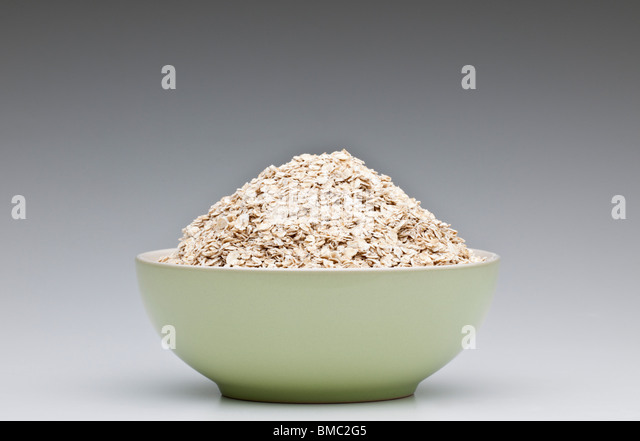 Green breakfast bowl heaped full of porridge oats - Stock Image