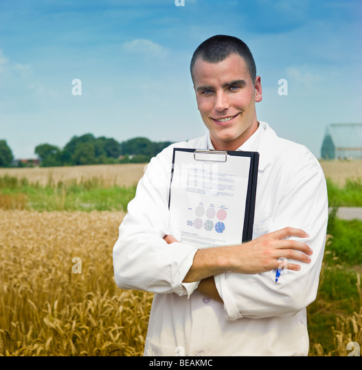 Agriculture scientist making notes in the field with greenhouses in background - Stock Image