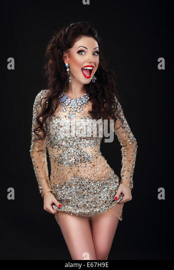 Cheerful Woman in Shiny Silver Stagy Dress Having Fun - Stock Image