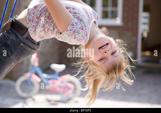 Young girl upside down on swing - Stock-Bilder