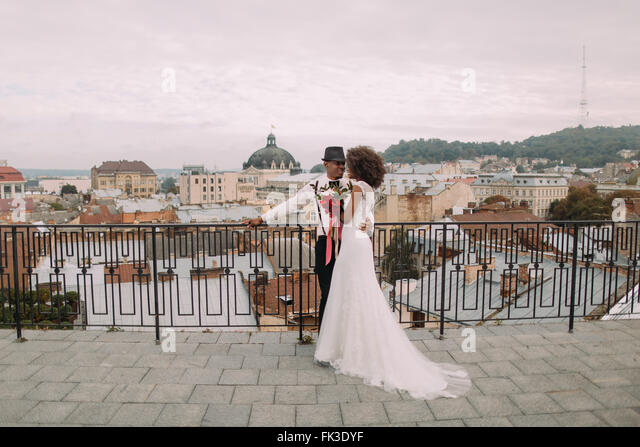 Happy black wedding couple softly hugging on the rooftop - Stock-Bilder