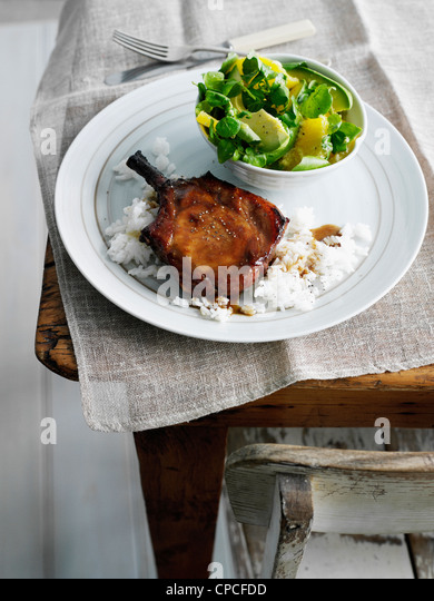 Plate of pork chop, rice and salad - Stock Image