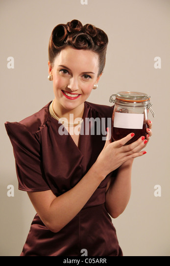 Old fashioned woman holding a jar - Stock-Bilder
