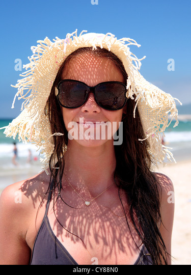 Attractive girl wearing hat and sunglasses on holiday at sunny beach - Stock Image