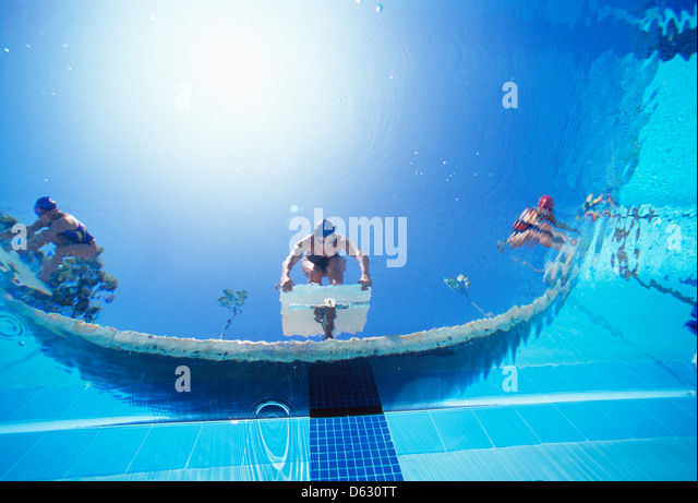 Low ngle view of female swimmers ready dive in pool from starting position - Stock Image