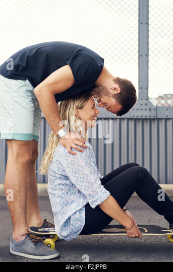 Man leaning over woman kissing her while she smiles - Stock-Bilder
