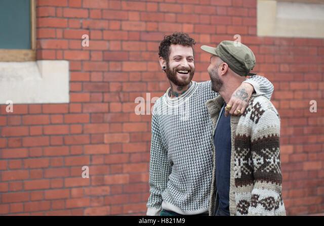 Gay couple arm in arm walking down the street - Stock-Bilder