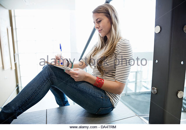 Female student writing notes in notebook at college campus - Stock Image