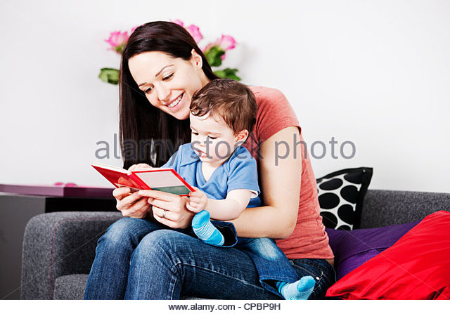 A mother and her baby son sitting on the sofa reading a book - Stock Image