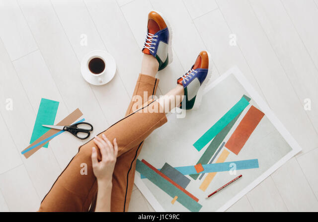 Legs of woman designer sitting on floor wearing multicolor shoes - Stock Image