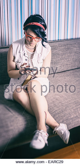 girl hipster have fun in vintage style fond of phone - Stock Image