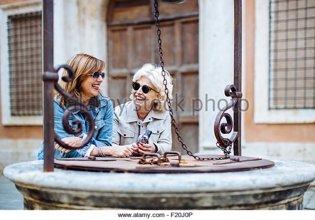 Two mature female friends chatting at water well, Tuscany, Italy - Stock Image