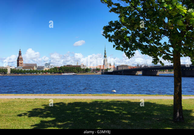 Panorama of Riga with spiers of churches and the bridge at the river Daugava in the background of green wood in - Stock Image