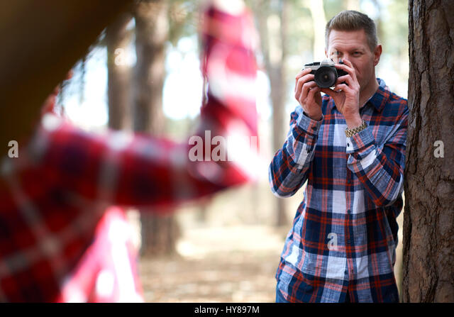A man takes a photo of his female companion as they walk in the woods - Stock Image