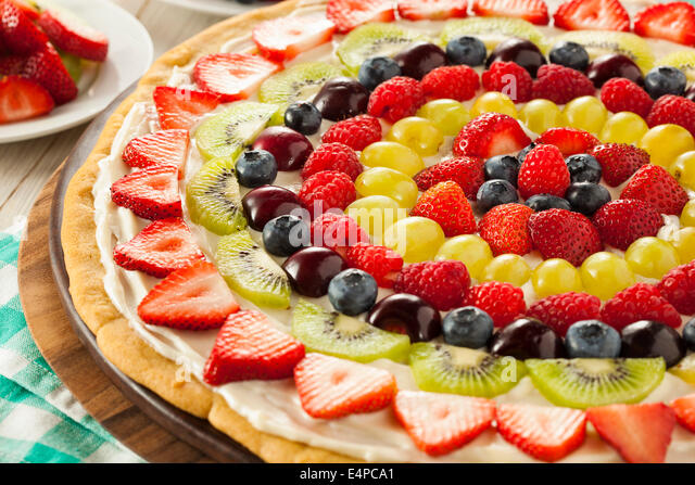 Homemade Natural Fruit Pizza with Frosting and Berries - Stock Image