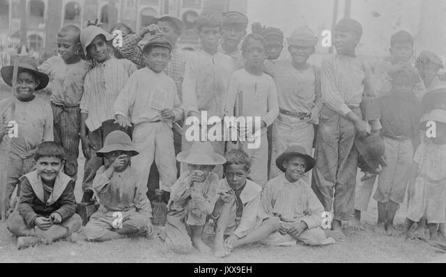 Full length landscape shot of young boys dressed in hats and casual clothing, some African American, all with smiling - Stock Image