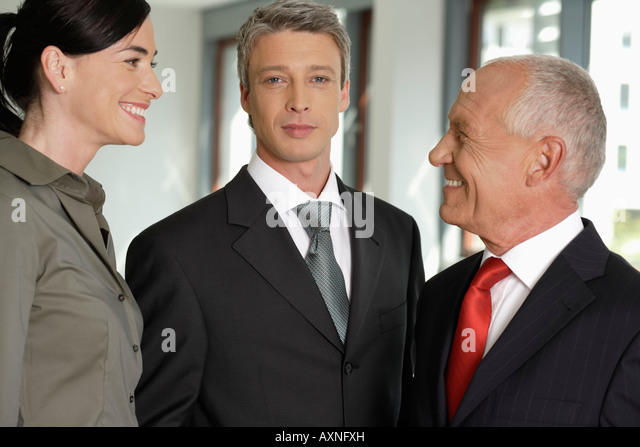 Business woman talking with two business men - Stock Image