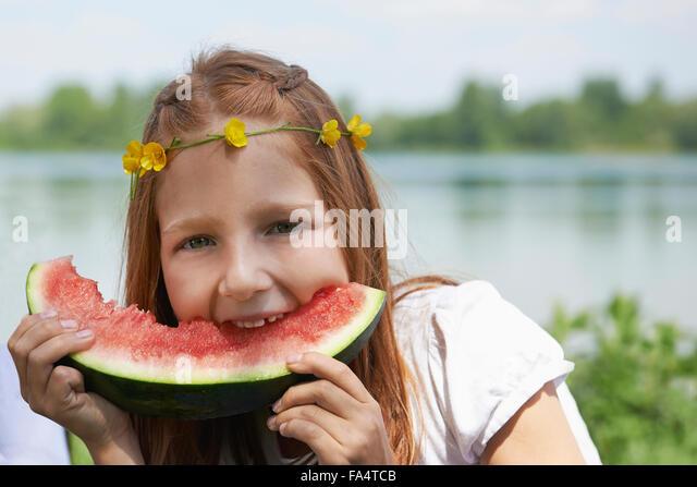 Girl enjoying slice of watermelon at picnic, Munich, Bavaria, Germany - Stock Image