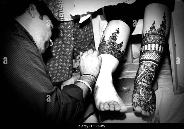 An Indian bride gets her ankles painted with henna in New Delhi in India. - Stock-Bilder