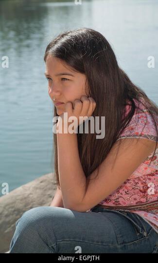 Hispanic-Caucasian teen girl 11-13  meditating, meditates thinking alone in natural setting . MR  © Myrleen - Stock-Bilder