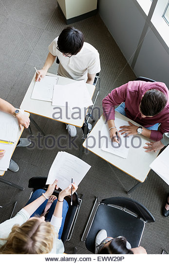 Overhead view college students studying in group classroom - Stock Image