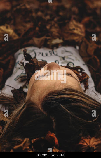portrait of the young girl lying in autumn leaves - Stock Image