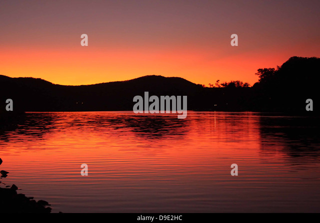 ORANGE YELLOW SUNSET ON WATER RIVER WEST BRANCH SUSQUEHANNA, LOCK HAVEN, CLINTON COUNTY,  PENNSYLVANIA, USA - Stock Image