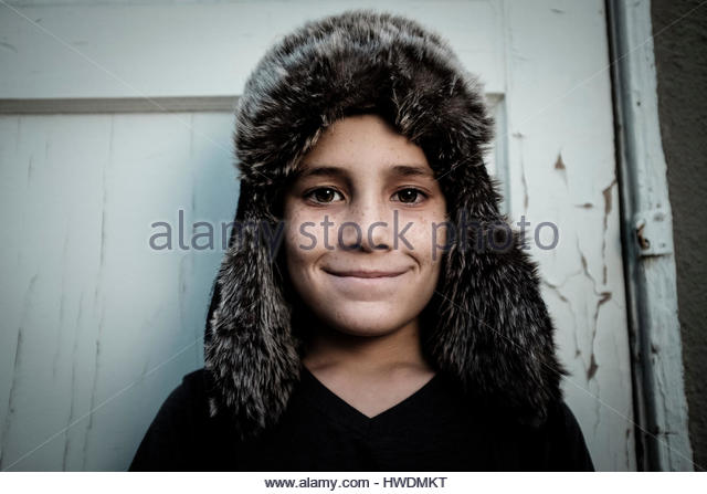 Boy wearing trappers hat standing against door - Stock-Bilder