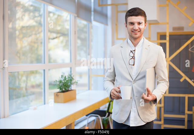 Happy worker in workplace - Stock Image