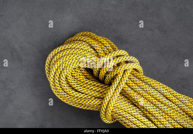 Yellow rock climbing dynamic rope on dark background - Stock Image