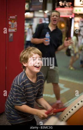 nine year old american boy plays taiko drum video game in Shinjuku, Tokyo Japan, video arcade with father cheering - Stock-Bilder
