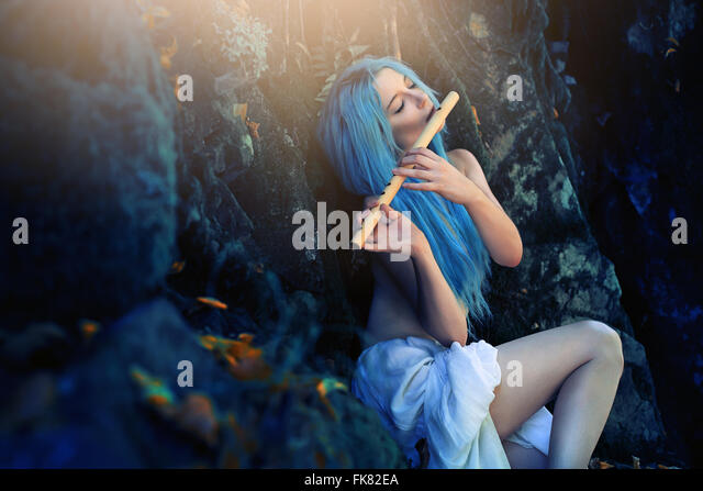 Beautiful ethereal creature of the forest playing flute . Fantasy and surreal - Stock-Bilder