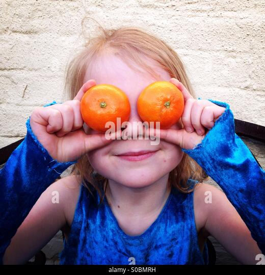 Happy child with oranges as eyes. Girl holding too soft oranges over her eyes. - Stock Image