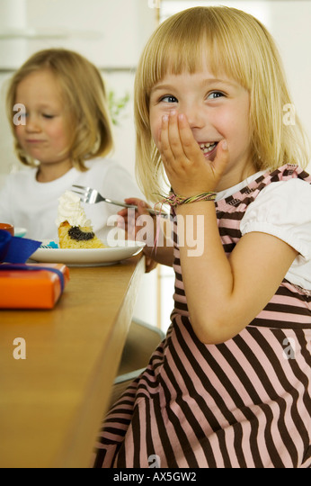 Two girls (4-5) eating cake in kitchen - Stock Image
