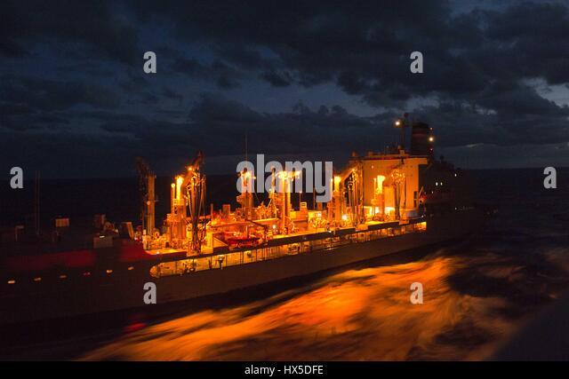 Lit with a fiery glow in the night, Military Sealift Command fleet replenishment oiler USNS Leroy Grumman (T-AO - Stock Image