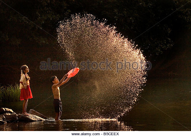 CHILDREN PLAYING BY THE RIVER - Stock-Bilder