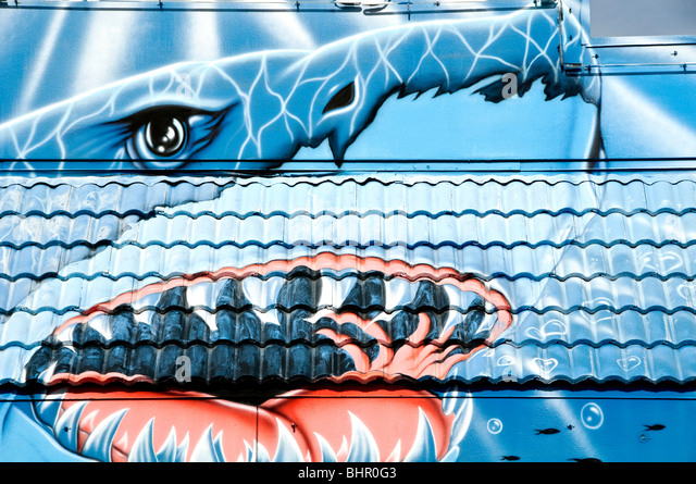 Giant shark with mouth open showing sharp teeth painted on blue metal roof outdoors - Stock Image