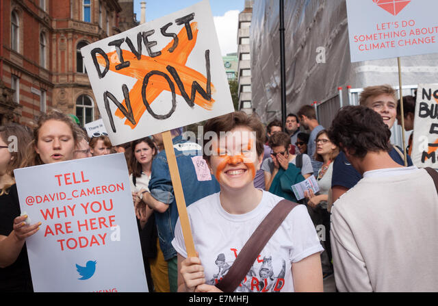 A young demonstrators smiles as he holds a placard, calling for institutions across the country to divest from fossil - Stock Image