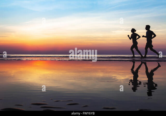 two runners on the beach, silhouette of people jogging at sunset, healthy lifestyle background with copyspace - Stock Image