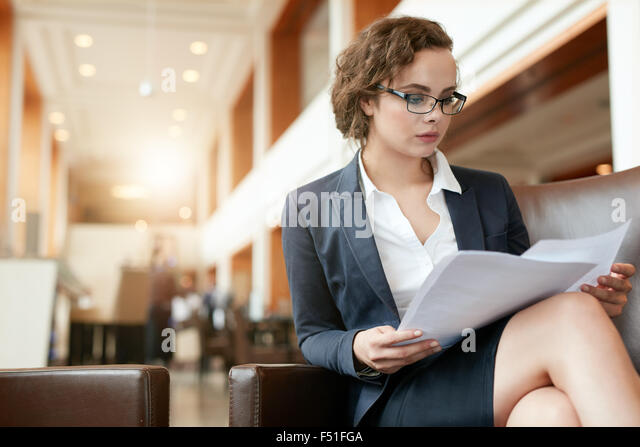 Portrait of businesswoman reading document. Female professional in hotel lobby examining papers. - Stock Image