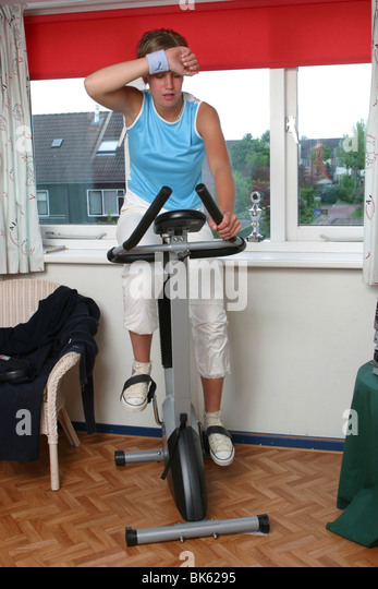 Young woman fitness training at home on stationary bicycle - Stock Image