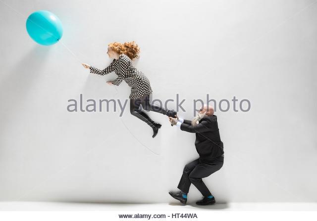 Businessman pulling leg of businesswoman holding blue balloon against white background - Stock-Bilder
