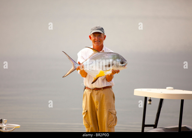 Portrait of fisherman holding a caught fish - Stock Image