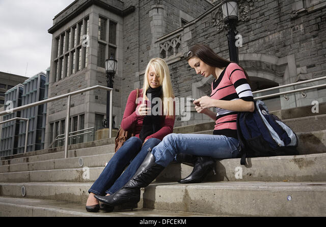 Two female college students sitting on the steps of a building texting on the cell phones, University of British - Stock Image