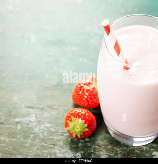 A glass of strawberry smoothie on a wooden background - Stock Image